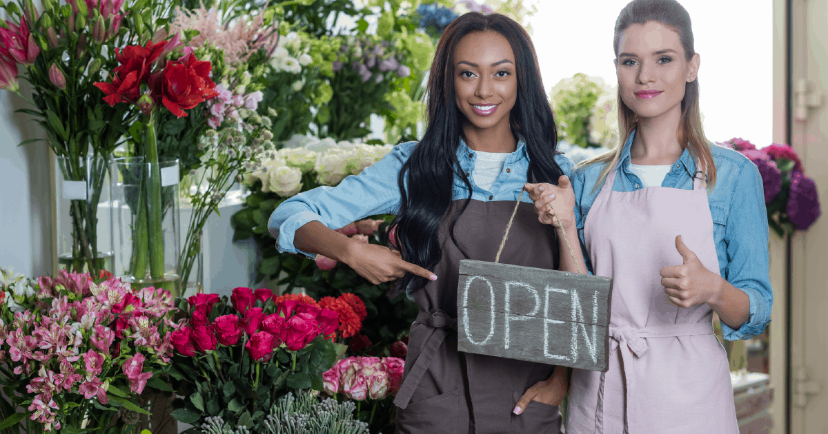 business owners gesturing that business is open