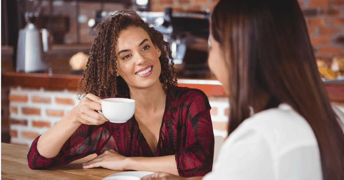 Woman exhibiting relationship selling over a cup of coffee